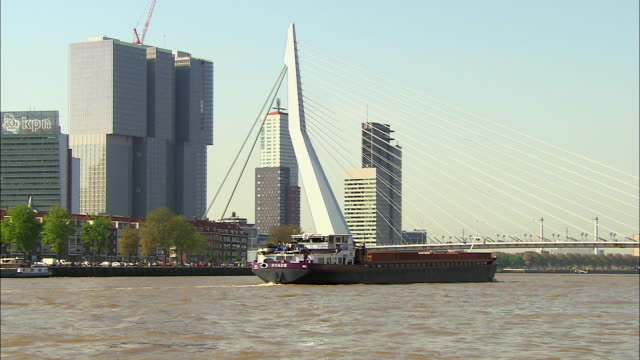 zoom out of barge moving past erasmus bridge - cable stayed bridge stock videos & royalty-free footage