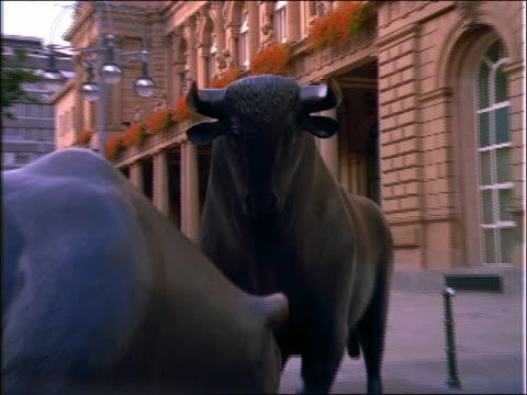 zoom out of black bull + bear statues in front of building / frankfurt - växtätare bildbanksvideor och videomaterial från bakom kulisserna