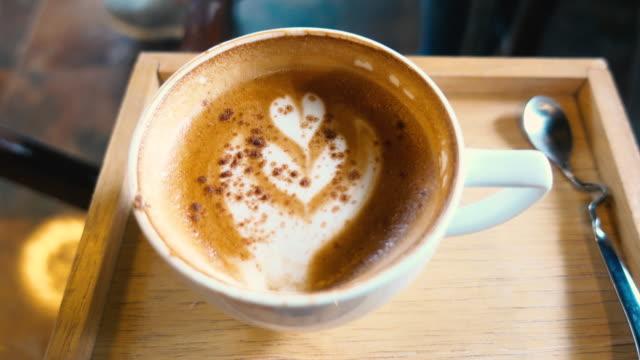 ぼかしコーヒー カフェのコーヒー カップでラテアートが縮小されます。 - カフェイン分子点の映像素材/bロール