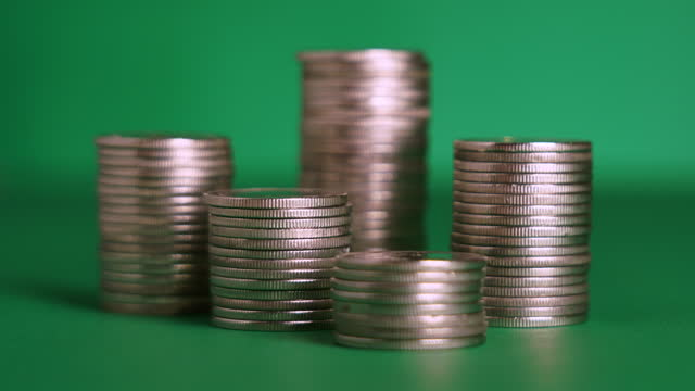 zoom out of coins stack on green background - us coin stock videos & royalty-free footage
