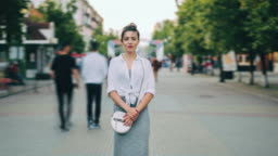 Zoom out of good-looking young lady standing alone on street looking at camera