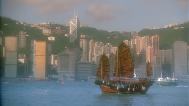 zoom out of junk in harbor with hong kong skyline in background / central district / diffusion filter - central district hong kong stock videos & royalty-free footage