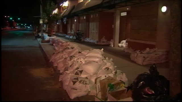 zoom out of line of sandbags on sidewalk - environment or natural disaster or climate change or earthquake or hurricane or extreme weather or oil spill or volcano or tornado or flooding stock videos & royalty-free footage