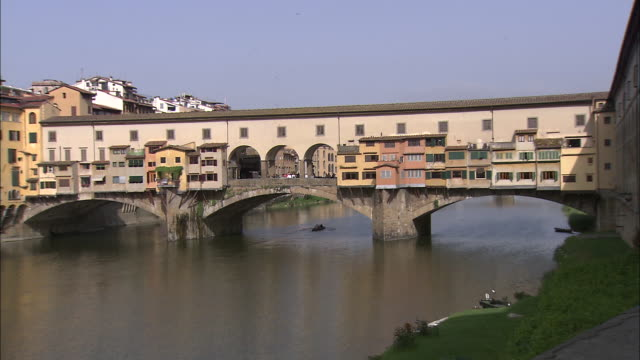 zoom out of men rowing on river to ponte vecchio - ponte点の映像素材/bロール