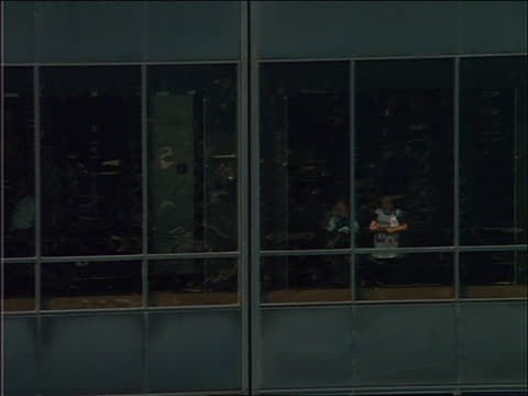 aerial zoom out of people looking out window of building / chicago - fensterfront stock-videos und b-roll-filmmaterial