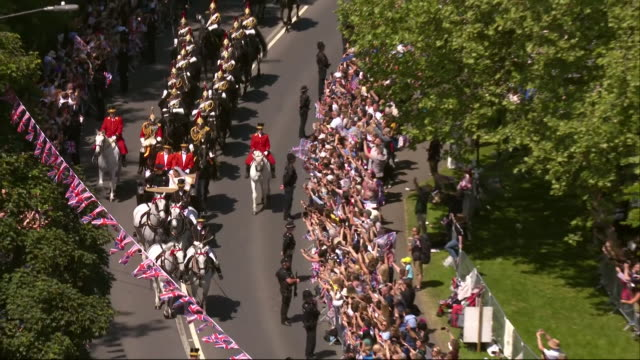 Zoom out of the escorted carriage containing the newlywed Duke and Duchess of Sussex rounding a corner onto the Long Walk in Windsor Great Park