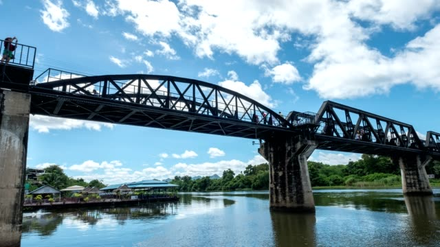 zoom out of train running on river kwai bridge with railway station - bretagna video stock e b–roll