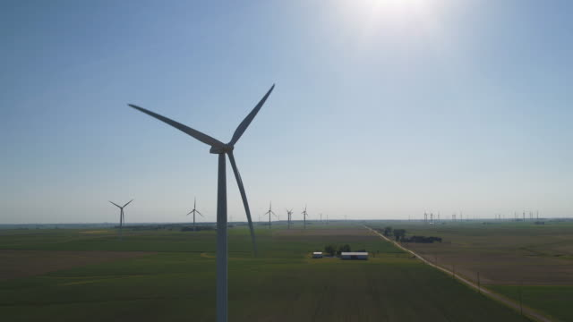 Zoom out of wind turbines in sunny field
