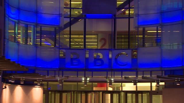 zoom out on bbc logo on exterior of new broadcasting house at night - zoom out stock videos & royalty-free footage