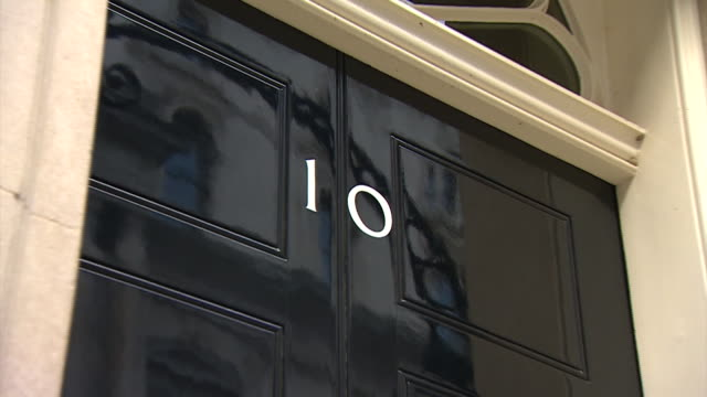 Zoom out on the door of 10 Downing Street being closed