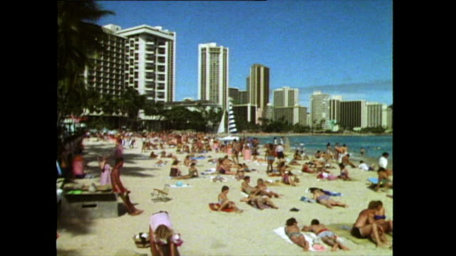 zoom out over crowded waikiki beach in hawaii; 1985 - zoom out stock-videos und b-roll-filmmaterial