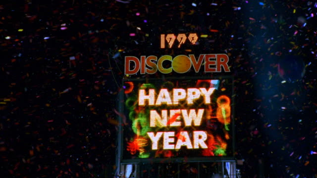 "zoom out pan ""happy new year"" sign, confetti and cheering crowd in times square at night on new year's eve - 1999 stock videos & royalty-free footage"