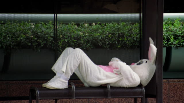 Zoom out pan medium shot man in rabbit costume lying on bench in bus shelter while waiting / L.A.
