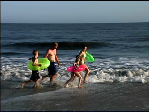 zoom out pan right of a family running through the ocean surf. they are all wearing bathing suits and the children and mom are carrying innertubes. - see other clips from this shoot 1135 stock videos & royalty-free footage