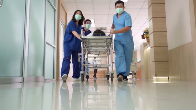 4k uhd zoom out standpunkt flachwinkelaufnahme: patient auf krankenhaus-gurney-tragebett wird vom medizinischen team den flur des krankenhauses hinunter transportiert. - moving down stock-videos und b-roll-filmmaterial