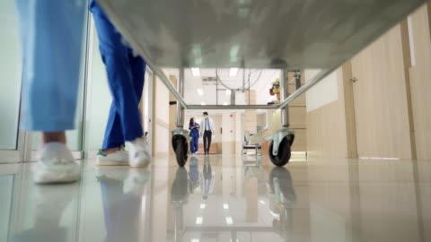 vídeos y material grabado en eventos de stock de 4k uhd zoom out punto de visión tiro de ángulo bajo: paciente en cama camilla de camilla del hospital siendo transportado por el pasillo del hospital por el equipo médico. - esfuerzos problemas