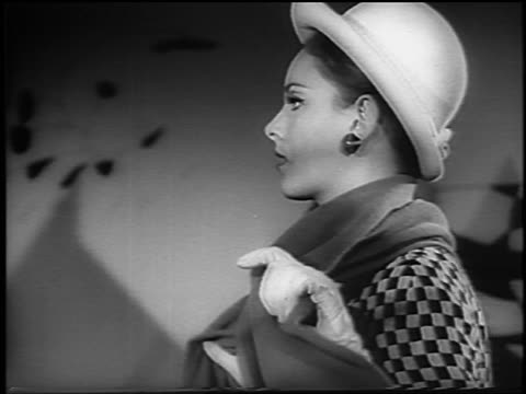 b/w 1965 zoom out profile female model in hat + checkered coat removing scarf / moma / newsreel - anno 1965 video stock e b–roll
