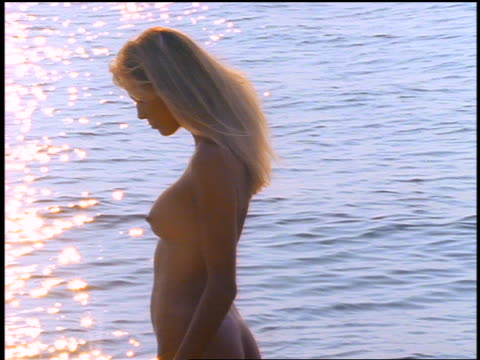 zi, zoom out pan profile nude woman walks from body of water to shore / corsica - beautiful woman stock videos & royalty-free footage