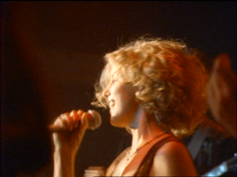 zoom out profile woman singing on stage with microphone / backup singers in foreground - pop musician stock videos and b-roll footage