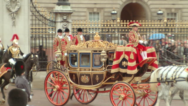 vídeos de stock e filmes b-roll de zoom out pan royal carriage with queen leaving buckingham palace with royal guards on horseback following - realeza