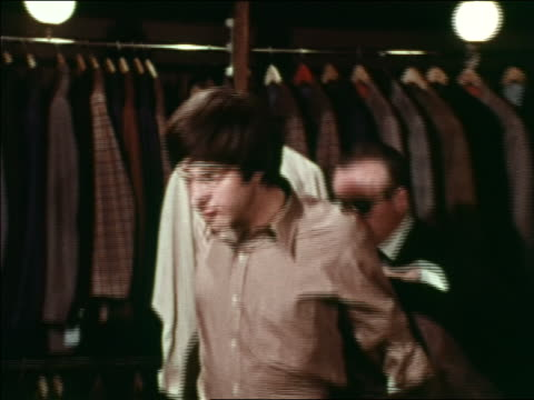 1969 zoom out salesman helping man try on sports jacket in clothing store / nyc / industrial - clothes shop stock videos & royalty-free footage