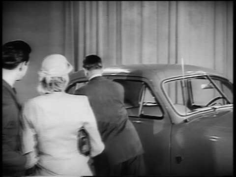B/W 1950 zoom out salesman opening door for couple to get in Ford car in showroom