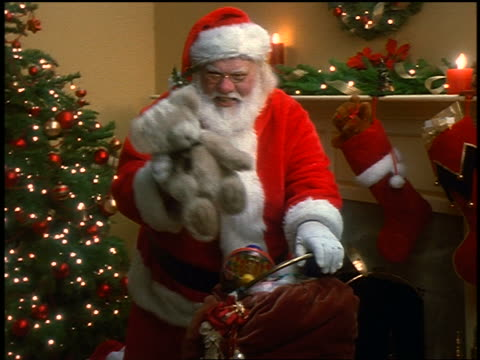 zoom out santa claus taking stuffed bear from bag + putting it under christmas tree in living room - サンタクロース点の映像素材/bロール