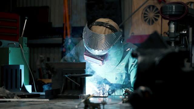 金属片を溶接中期成人男性のショットをズームアウト - 専門性点の映像素材/bロール