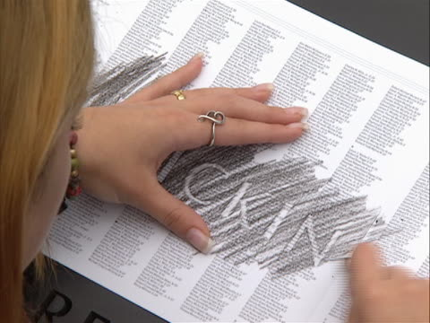 vídeos y material grabado en eventos de stock de zoom out shot of a woman tracing a name in crayon at the 9-11 memorial on the morning of 9/11/11, the tenth anniversary of the attacks. the names of... - 0 11 months