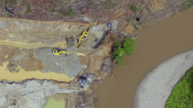 stockvideo's en b-roll-footage met zoom out shot of backhoes digging at illegal gold mine, colombia - verboden