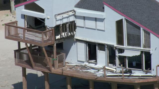vidéos et rushes de zoom out shot of storm damage to beach house on west beach in galveston, texas. - toit en tuiles