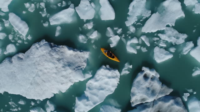 stockvideo's en b-roll-footage met zoom out shot of woman kayaking between icebergs in water, alaska, usa - alaska verenigde staten
