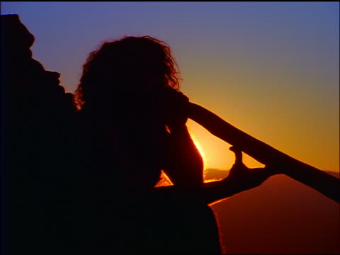 vidéos et rushes de zoom out silhouette sitting male aborigine playing didgeridoo / sunset in background / blue mountains, australia - australie