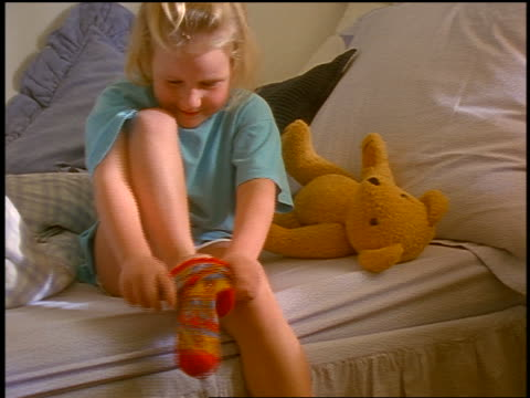 zoom out small blonde girl sitting on bed putting on sock - socke stock-videos und b-roll-filmmaterial