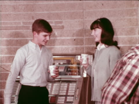 vidéos et rushes de 1965 zoom out teen couple dancing + drinking from paper cups by juke box at ymca dance / educational - couple d'adolescents