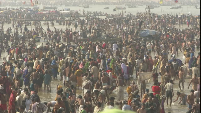 Zoom out through large crowds of Kumbh Mela pilgrims gathered at banks of Ganges, India