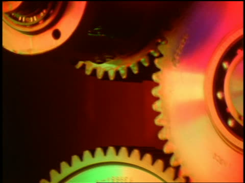 zoom out tilt down close up gears turning with changing lights