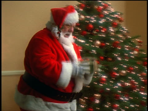 zoom out tilt down santa claus putting gifts under christmas tree in living room - einzelner senior stock-videos und b-roll-filmmaterial