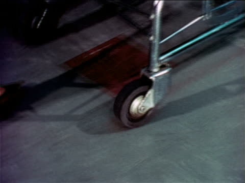 1965 zoom out tilt up from wheel of shopping cart to woman pushing it in grocery store aisle / educational - shopping trolley stock videos & royalty-free footage