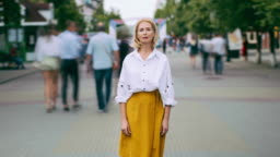 Zoom out time lapse of pretty mature woman looking at camera standing in street