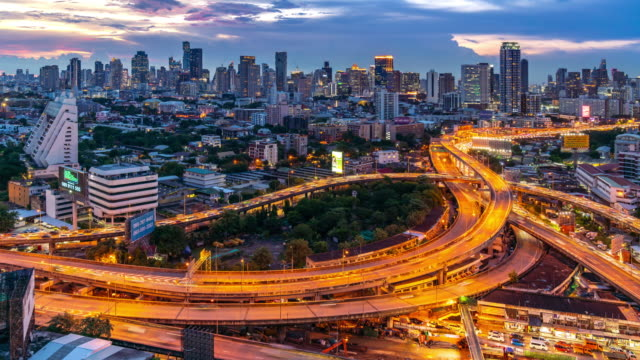 4k uhd zoom out time-lapse: bangkok highway traffic sunset with downtown skyscraper buildings skylines in background. transportation and modern cityscape concept. - motorway junction stock videos & royalty-free footage