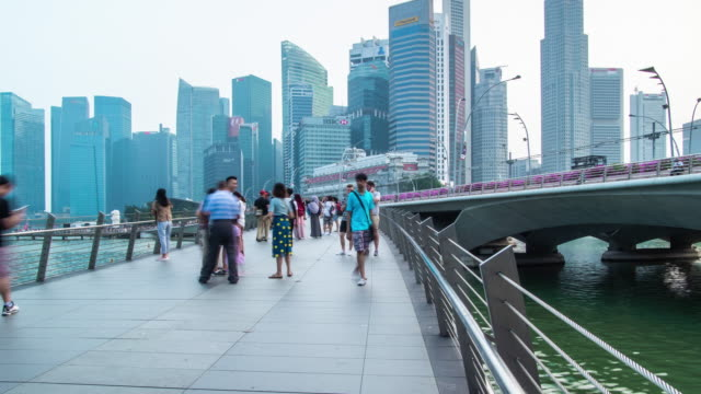 zoom out timelapse of pedestrian walkway around marina bay in singapore - river singapore stock videos & royalty-free footage