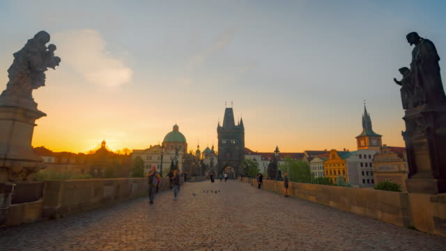 vídeos de stock e filmes b-roll de zoom out time-lapse : sunrise at chales bridge prague old town tower river czech republic - república checa
