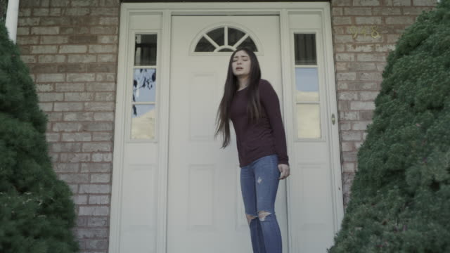 zoom out to close up of depressed girl leaving house and sitting on front stoop / springville, utah, united states - springville utah stock videos & royalty-free footage