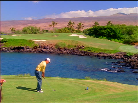 zoom out to wide shot male golfer teeing off over water with second male golfer watching / mountains in background / hawaii - teeing off stock videos & royalty-free footage