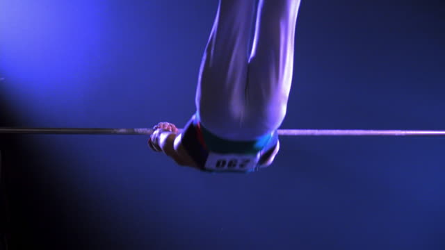 zoom out to wide shot male gymnast peforming on the high bar and dismounting - horizontal bar stock videos and b-roll footage