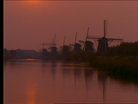 zoom out to wide shot of silhouette of windmills on riverbank / holland / orange filter - romantische stimmung stock-videos und b-roll-filmmaterial