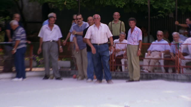 zoom out to wide shot senior man throwing bocci ball on court as group of men watch / milan, italy - italian culture stock videos & royalty-free footage