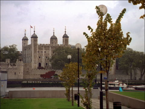 zoom out to wide shot tower of london with boats on thames river in foreground / london, england - ausflugsboot stock-videos und b-roll-filmmaterial