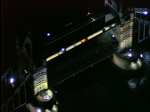 aerial zoom out tower bridge on river thames at night / london - 1997 stock videos & royalty-free footage